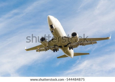 white plane takes off from the runway on the background of blue sky