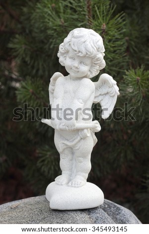 White plaster figurine Angel Cupid on a fir-tree background. - stock photo