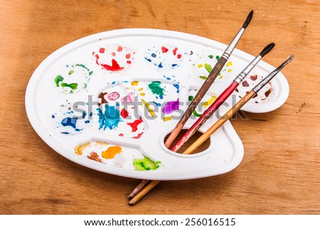 White plastic art palette with random watercolor paint blobs and brushes on wood - stock photo