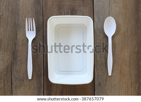 White plastic bowl and have spoon,fork on old wood background.