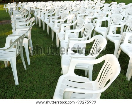 White plastic chairs arranged in rows on green grass for an outdoor wedding or graduation. - stock photo