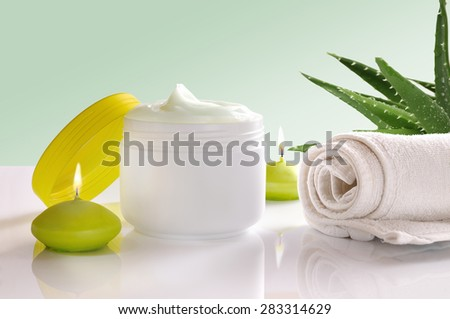 White plastic container with facial or body cream of aloe vera. Candles, towel and plant decoration and green background isolated. Front view - stock photo