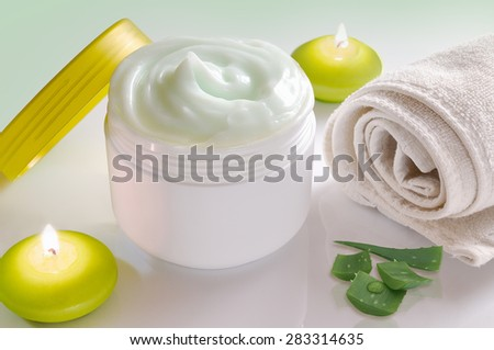 White plastic container with facial or body cream of aloe vera. Candles, towel and plant decoration and green background isolated. Top view - stock photo