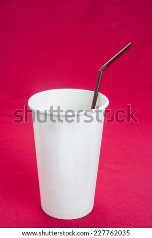 White plastic cup isolated on red background