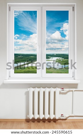 White plastic double door window with radiator under it. Landscape in view - stock photo