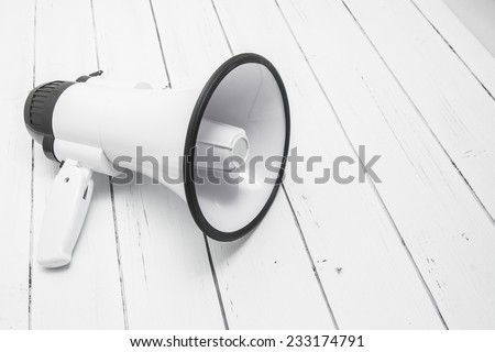 White plastic megaphone isolated on a white wooden background.  - stock photo