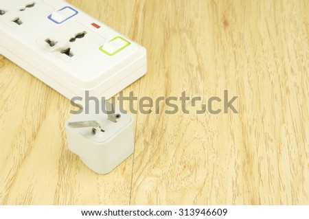 White plastic plug burned because use overload on wood background.