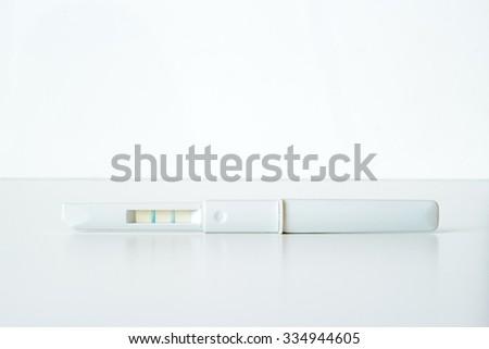 White plastic positive pregnancy test on white background - stock photo