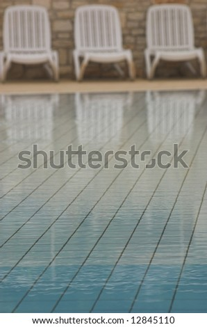 White plastic seats standing on a terrace next to a pool