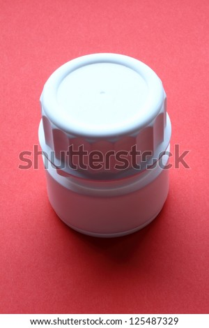 white plastic vessel for pills collection on red background - stock photo