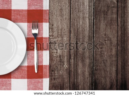white plate and fork on old wooden table with red checked tablecloth and copyspace - stock photo