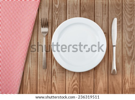white plate and fork on old wooden table with red cloth - stock photo