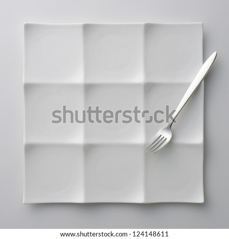 white plate and fork on white table - stock photo