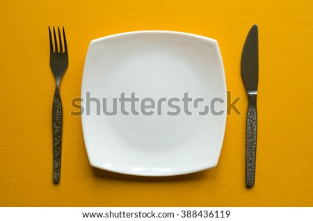 White plate, fork and knife on a yellow background.