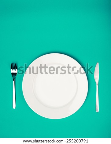 white plate, fork and knife on emerald background - stock photo