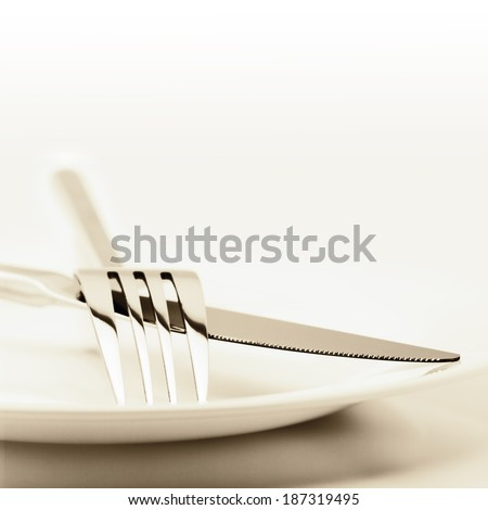 White plate, fork and knife on light background. Toned image. - stock photo