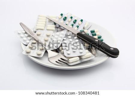 White plate full of pills - stock photo