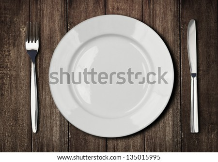 white plate, knife and fork on old wooden table - stock photo