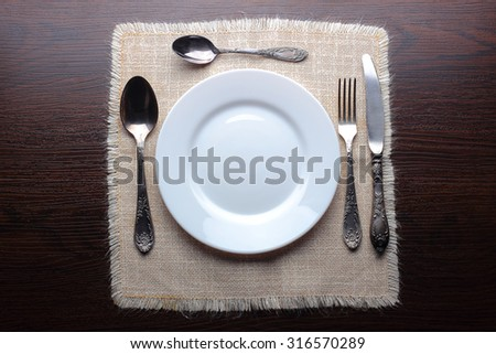 White plate, knife, fork and spoons at napkin on wooden background - stock photo
