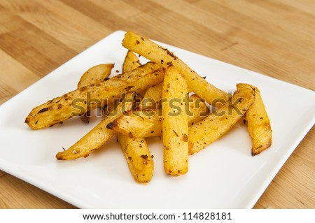 White plate of rutabaga fries on wood