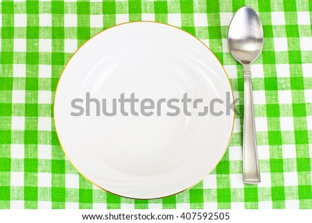 White Plate on a Checkered Tablecloth with Place for Your Text Studio Photo - stock photo