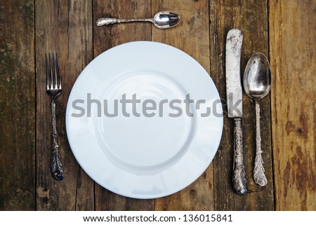 white plate on an old wooden table with antique cutlery