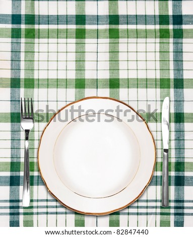 white plate on green checkered tablecloth with knife and fork - stock photo