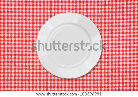 White plate on red and white tablecloth background