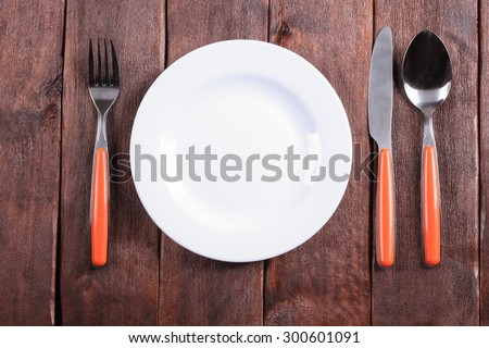 White plate on the table. Empty plate. Fork, knife and spoon on the table. Laying the table. Starvation diet. Template, background, space for text. Restaurant, catering, cafeteria. For food. - stock photo