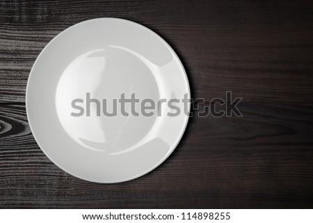 white plate on the wooden brown table - stock photo