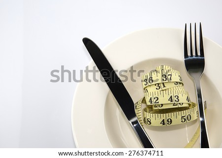 White plate with a knife and fork with measuring tape on white background, diet concept