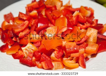 White plate with chopped red sweet pepper - stock photo