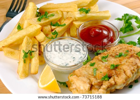White plate with fish and chips, mayo, lemon and ketchup - stock photo