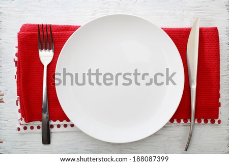 White plate with fork and knife on red napkins - stock photo