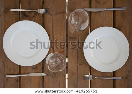 White plate with fork knife and whine glasses on wooden background