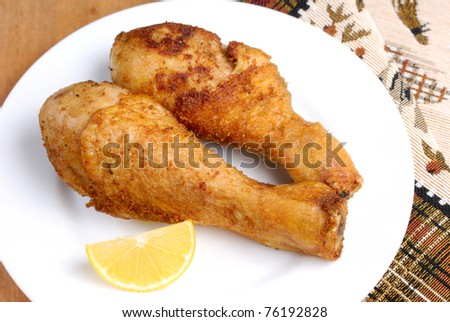 White plate with fried chicken drumsticks