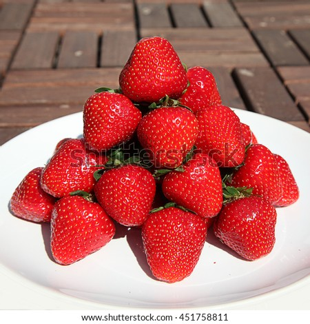 white plate with heap of red ripe strawberries - stock photo
