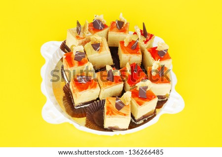 White plate with some small delicious cakes at yellow background. - stock photo