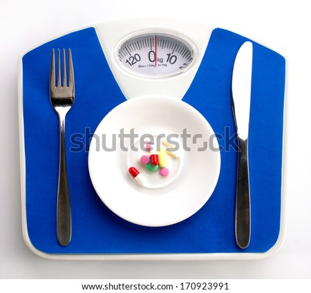 white plate with supplement, spoon and knife on blue scale, top view - stock photo
