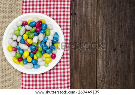White plate with sweet color candy on old wooden table with red checked tablecloth and copy space - stock photo
