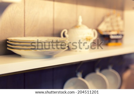 White plates and dinnerware in a cupboard - stock photo