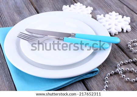 White plates, fork, knife and Christmas tree decoration on wooden background - stock photo