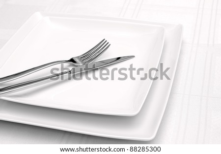 White plates on white tablecloth