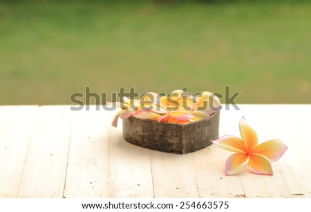 White Plumeria flowers on wood background. - stock photo