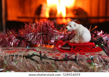 White polar bear on the red sleigh with a fireplace on the background