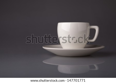 white porcelain cup and saucer on a gray background