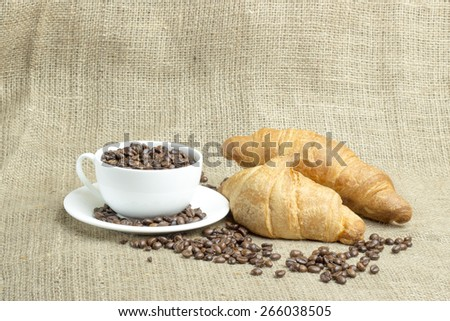 White porcelain cup filled with coffee beans, two croissants, coffee beans, burlap - stock photo