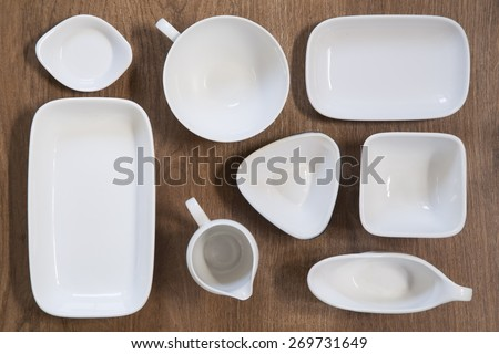 White porcelain dishes on wooden background - stock photo