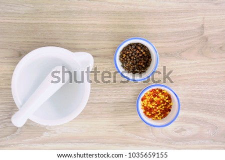 White porcelain mortar and pestle with dried peppers in flat lay and shot in natural light