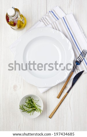 white porcelain plate and striped napkin on a white  wooden background - stock photo